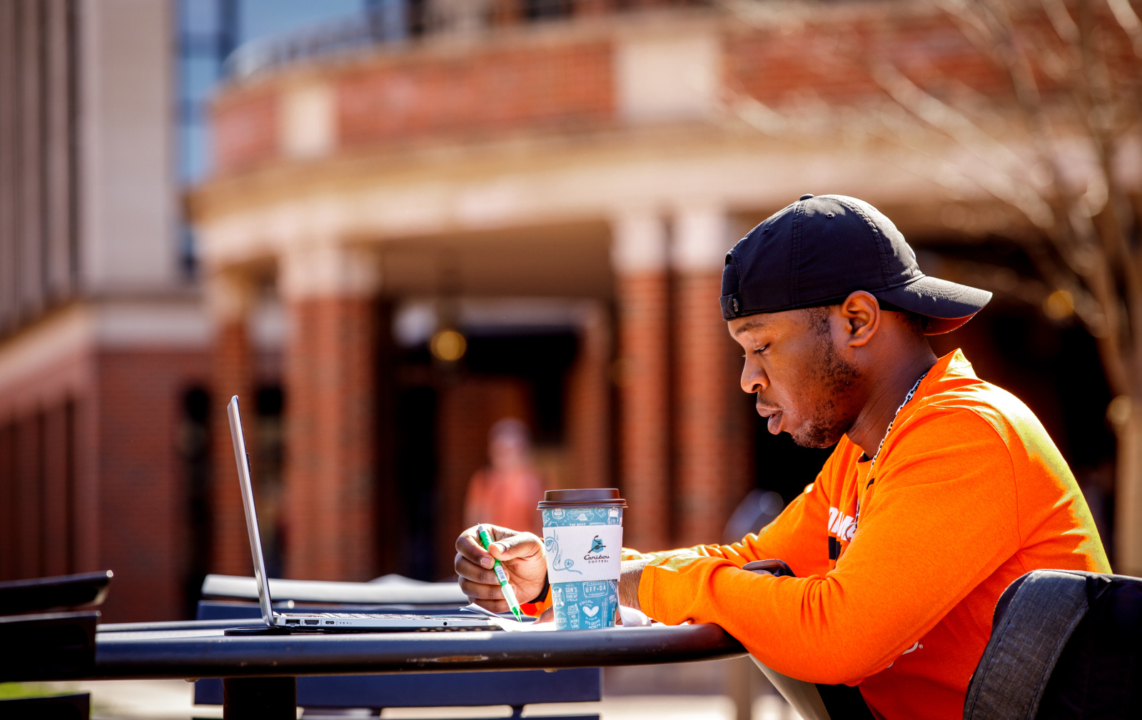 Student on their laptop studying in the Student Union courtyard on the OSU campus in Stillwater.